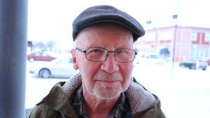 En äldre herreman med keps och glasögon.