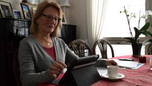 Inger Wretdal med papper på bordet som har en röd bordduk. Fotat lite i motljus, Wretdal knäpper på sin dator och har en massa papper på bordet.