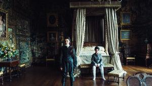 Drottning Anne sitter framför sin enorma säng med hertginnan Sarah stående i förgrunden.