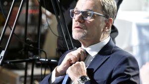 Juha Sipilä spänner kravatten 2019.