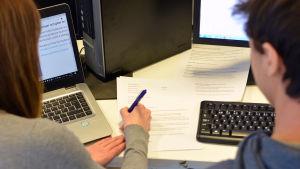 En kvinna sitter med penna och papper och försöker lära en kille att skriva CV.