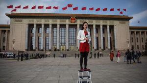 En journalist står på en pall då hon rapporterar utanför Kinas folkongress i Peking