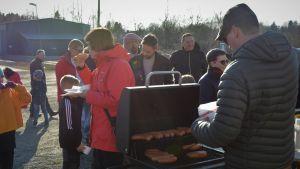 En man serverar grillad korv till flera människor som står i kö.