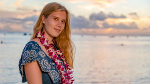 Au pair Annika seisoo ilta-auringossa rannalla lei kaulassaan.