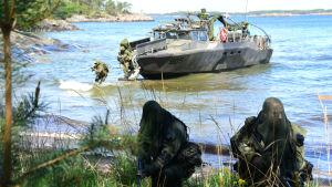 militär personal under övning vid strand