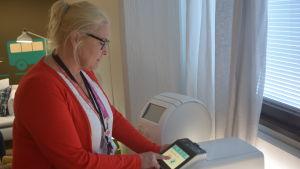 Viveka Bergdahl-Silvennoinen, som jobbar som teamförman på Helsingfors stads servicecentral, visar upp hur en läkemedelsrobot fungerar