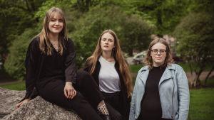 Tre av medlemmarna i årets jury för svenska yles litteraturpris poserar för kameran i en somrig park.