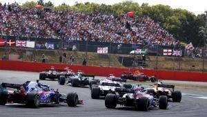 F1-bilar kör i en kurva i Silverstone framför fullsatt läktare.
