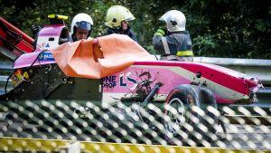 En kvaddad formel 2-bil står på en bärgningsbil, i bakgrunden står brandmän
