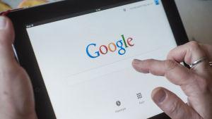 en kvinna googlar något på sin tablet