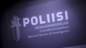 """En skylt med polisens logo som föreställer ett svärd med det finska lejonhuvudet. Previd logon ses texten """"Polis"""" och """"Centralkriminalpolisen"""""""