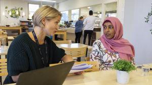 Projektarbetare Maija Tanneraho på yrkesinstitutet Careeria funderar på lämplig praktikplats med Sadio Abdiramaan.