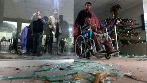 Pyörätuolissa istuvaa naista työnnetään lasinsirpaleiden ohi.