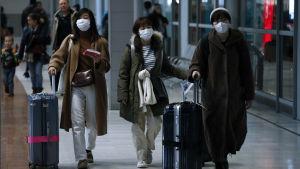 Tre damer iklädda ytterrockar och munskydd drar på var sin kappsäck i en flygplatskorridor.