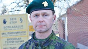 En bild på en man som står framför ett staket. Han är klädd i militäruniform.