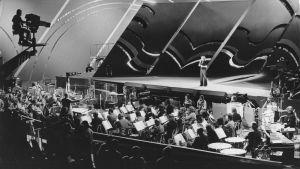Norjalainen Ellen Nikolaysen lavalla Euroviisuissa vuonna 1975. Mustavalkoisessa kuvassa näkyy myös orkesteri.