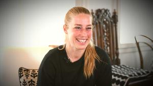 Linda Sällström skrattar hemma i soffan då hon blir intervjuad