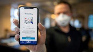 En man håller fram sin mobiltelefon. På mobilskärmen syns en coronavirusapp.