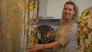 Kvinna öppnar vattenkran i ett litet kök.