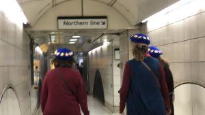 Tre damer med EU-hattar vandrar i Londons underground-gångar på väg till en demonstration för EU och mot brexit den 20 oktober 2018.