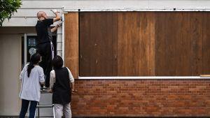 En man isolerar sitt hus med bräder för att skydda det från att skadas i stormen Haishen i staden Kagoshima i Japan.