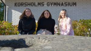 Tre unga kvinnor sitter på en bänk. I förgrunden
