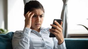 En bekymrad kvinna tittar på sin telefon.