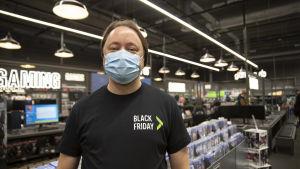 """En anställd vid elektronikaffären Gigantti som står inne i butiken med munskydd på sig. Personen har en t-skjorta på sig där det står """"black friday""""."""