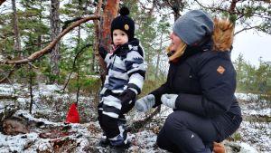 Ett barn och en kvinna står invid en liten tall. På marken syns en röd tomteluva.