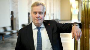 Antti Rinne tittar in i kameran och ler smått. Han lutar med ena armen mot ett dörrhandtag i riksdagen den 14.12.2020.