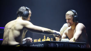 Shakkinyrkkeilyn shakkierää pelaavat paidattomat miehet