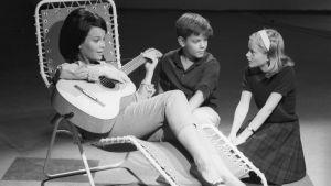Carola Standertskjöld soittaa lepotuolissa kitaraa ruotsinkielisessa lastenohjelmassa.