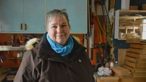 Claire Witick-Mäkelä står i sitt förråd med inredning från 1970-talet.