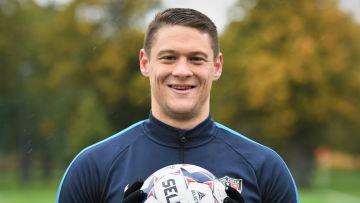 En leende Filip Valenčič poserar med fotboll i händerna.