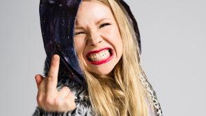 Elli (Anna-Riikka Rajanen) näyttää kameralle keskisormea hampaat irvessä.