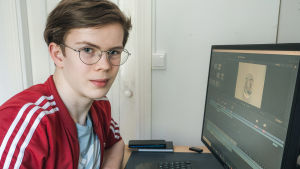 pojke sitter vid dator