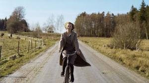 Den unga Astrid cyklar på landsvägen.