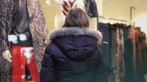 En person i vinterjacka tittar in genom ett skyltfönster till en klädbutik.