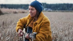 Kvinna i gul jacka och blå mössa sjunger och spelar gitarr mitt i sädesfält.