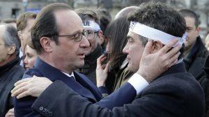 Frankrikes president Francois Hollande kramar en kolumnist vid Charlie Hebdo under manifestationen mot terrorism i Paris 11.1.2015