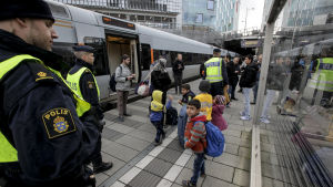 Svensk polis kontrollerar resenärer i Malmö.