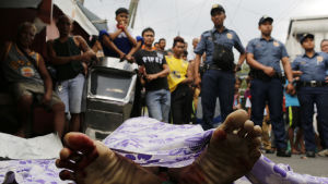 Filippinsk polis vaktar liket av en skjuten misstänkt droghandlare.