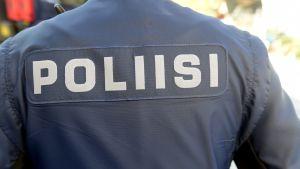 Polis med ryggen vänd mot kameran