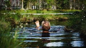 Toimittaja Nicke Aldén selin kameraan uimassa turvelähteessä Nummijärven Kammi-kylässä.