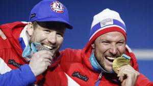 Kjetil Jansrud och Aksel Lund Svindal biter i sina medaljer.