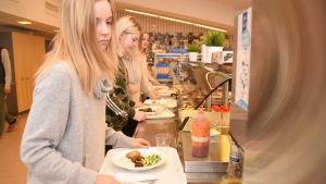 Matilda Hellström och Ida Bäckström tar åt sig mat i skolmatsalen i Källhagens skola i Virkby.