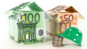 Två hus byggda av sedlar och en hjälm som lutar på en mynthög.