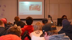 En grupp e-sportstuderande sitter koncentrerat och lyssnar på när Female Legends håller föredrag. I förgrunden finns utbildningens enda kvinnliga studerande.