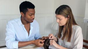 En man och en kvinna sitter vid ett bord. I händerna håller de löshår. De är make up-artister och hårstylister.