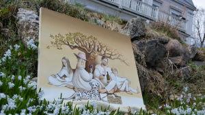 En tavla på en picnic. Tavlan ligger i gräset med blommor.